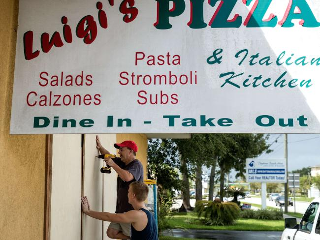 Patrick Sheehan boards up windows at his pizza shop in Ormond Beach, Florida. Picture: Drew Angerer/Getty Images/AFP.
