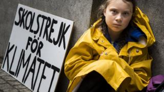 Greta Thunberg sits next to her school strike for climate sign
