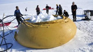 Flubber - rubber container- being filled with snow
