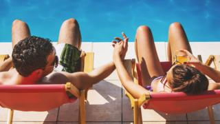 Holiday makers by a pool