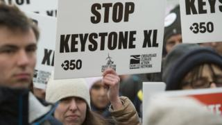A woman holds up a placard saying Stop Keystone XL