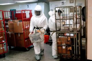 Pentagon officials wear protective suits as they inspect the quarantined mailroom