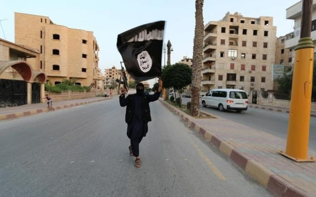 A member loyal to the Islamic State in Iraq and the Levant waves an ISIL flag in Raqqa