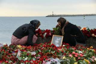 People lay flowers next to a portrait of Yelizaveta Glinka on the shore of the Black Sea in Sochi, 27 December