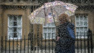 woman on umbrella in rain
