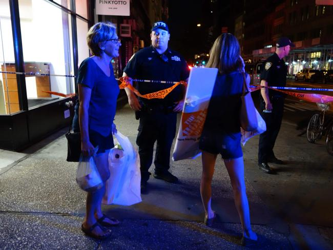 Two woman look on as police block a road after an explosion in New York's Chelsea neighbourhood. Picture: AFP / William Edwards