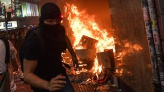 Protesters set fires outside Causeway Bay station in Hong Kong after the government banned face masks