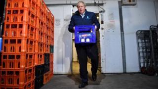 Boris Johnson carries crate of milk