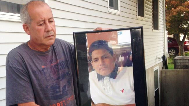 Abraham Chaparro, holds a photograph of his murdered stepson, Miguel Garcia-Moran. Picture: Claudia Torrens/AP