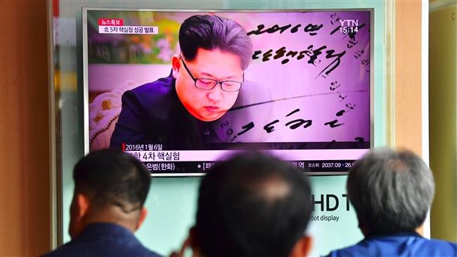 People watch a television news report showing file footage of North Korean leader Kim Jong-un at a railway station in Seoul