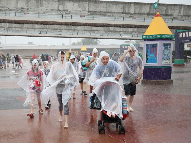 People leave Disney's Magic Kingdom theme park in heavy rain after it closed in Orlando, Florida in preparation for the landfall of Hurricane Matthew. Picture: Gregg Newton/AFP.