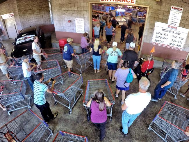 Shoppers crowd the entrance to the Costco store in Altamonte Springs, stocking up on essentials. Picture: Joe Burbank/Orlando Sentinel via AP.