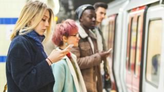 A woman looks at her phone on a tube platform in London