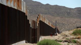 A Mexican family stands next to the border wall between Mexico and the United States, in Ciudad Juarez, Mexico on May 23, 2017