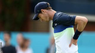 Andy Murray holds his back in pain