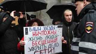 Protester holding a sign supporting the Set defendants outside FSB