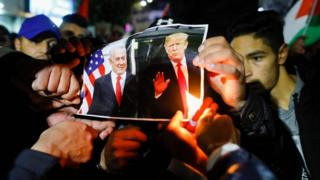 Palestinian protesters burn pictures of US President Donald Trump and Israel's Prime Minister Benjamin Netanyahu during a demonstration in the West Bank city of Ramallah