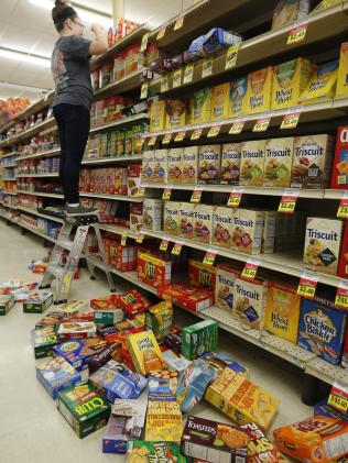 A supermarket worker cleans up after the earthquake. Picture: Paul Hellstern/The Oklahoman via AP