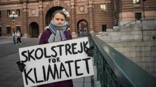 Greta holds her protest sign outside Swedish parliament