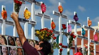 A relative of victims of the Casino Royale puts flowers on a cross during the commemoration of the first anniversary of the crime in Monterrey