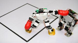 Two robots fight in a humanoid fighting competition during the 2016 China RoboWork Competition International Open at Rizhao Campus of Shandong Sport University on May 28, 2016 in Rizhao, Shandong Province of China.