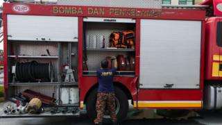 A firefighter moves hose after fighting with blaze in Kuala Lumpur, Malaysia