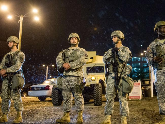Members of the National Guard watch as demonstrators march in the rain on September 22, 2016 in Charlotte, NC. Picture: AFP.