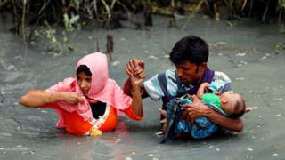 Rohingya refugees carry their child as they walk through water after crossing border by boat through the Naf River in Teknaf, Bangladesh, 7 September 2017
