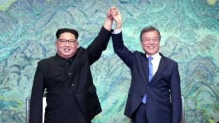 Kim Jong-un and Moon Jae-in raise their hands triumphantly at a Korean summit