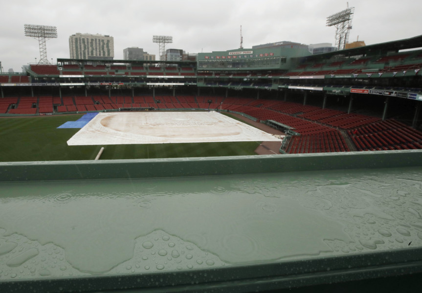 A tarp covers the infield and a puddle accumulates on the Green Monster ledge during steady rain at Fenway Park Sunday Oct. 9 2016 in Boston. Rain postponed Sunday's scheduled Game 3 of baseball's American League Division Series between the