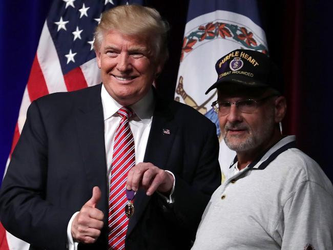 Republican presidential candidate Donald Trump (L) greets veteran Louis Dorfman (R), who gave Trump his Purple Heart. Picture: Getty