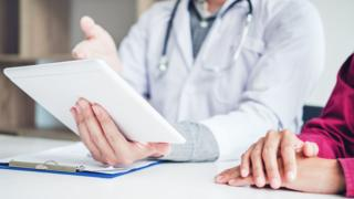 A doctor shows a patient medical information on a tablet computer