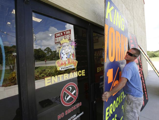 Andrew Esser boards up the glass doors at the entrance of Sky King Fireworks in Cocoa, Florida before Hurricane Matthew hits. Picture: AP Photo/John Raoux