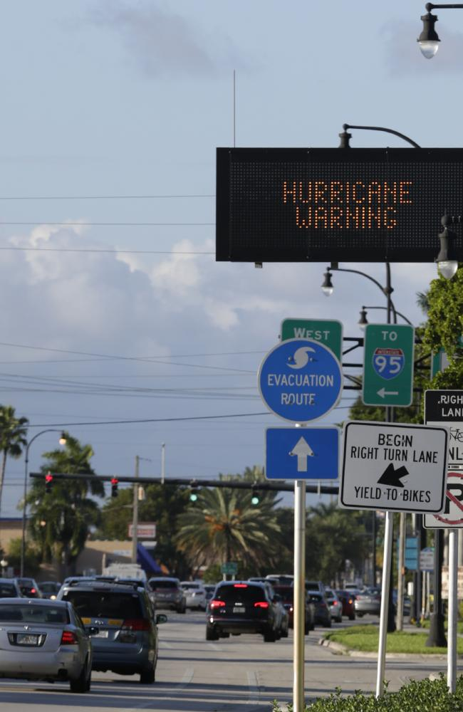 Motorists drive past a hurricane warning sign in Hallandale Beach, Florida. Picture: AP