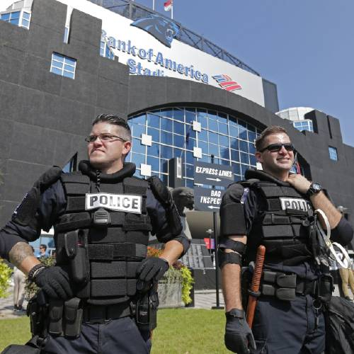 Police officers stand guard outside Bank of America Stadium before an NFL football game between the Carolina Panthers and the Minnesota Vikings in Charlotte N.C. Sunday Sept. 25 2016. Increased security is in place for