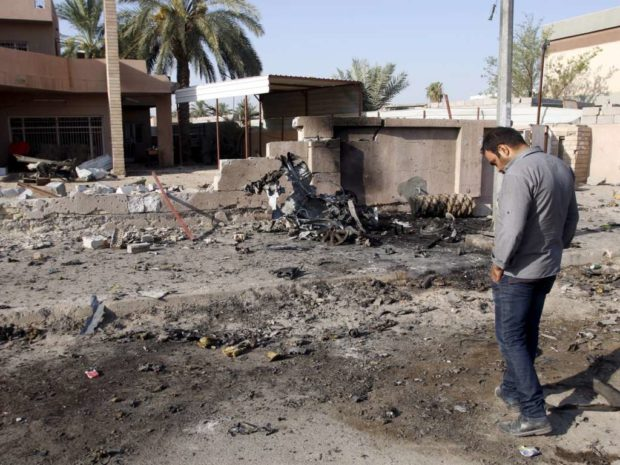 A resident inspects the site of car bomb attack in Baghdad