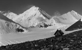 A snowy mountain shot including a small old-fashioned tent, captioned, Camp at 20,000 feet - the last day
