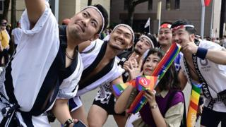 Participants pose for a selfie while taking part in the annual gay pride parade in Taipei