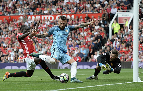 Manchester City's Argentinian defender Nicolas Otamendi attempts to shoot as Manchester United's Ivorian defender Eric Bailly defends and Manchester United's Spanish goalkeeper David de Gea dives during the English Premier League football matc
