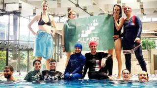 Members of the campaign group Citizen Alliance of Grenoble protest at a community pool in Grenoble, France