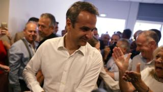 New Democracy conservative party leader Kyriakos Mitsotakis is greeted by supporters as he arrives at the party's headquarters in Athens