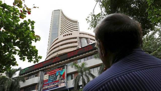 A man looks at a screen across a road displaying the Sensex on the facade of the Bombay Stock Exchange