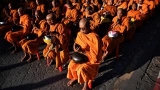 Buddhist monks gather for a mass prayer one week after a lone soldier shot and killed 29 people in Thailand