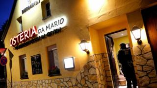 A sign on a yellow-painted two-story house declares this Italian restaurant to be Osteria Da Mario - but two police officers guard its open door in this dawn photo