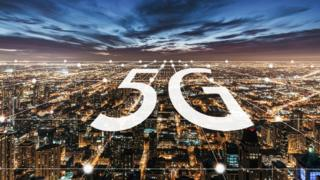 A stock image of a 5G logo over a big city