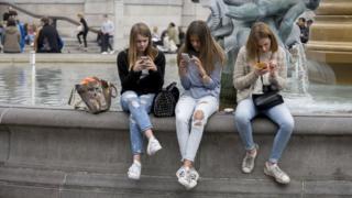 Teenage girls on smartphones in Trafalgar Square.