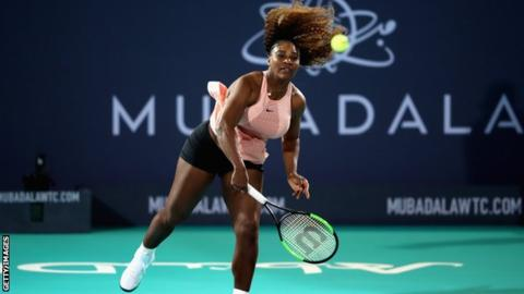 Serena Williams serves during her exhibition match against sister Venus in Abu Dhabi