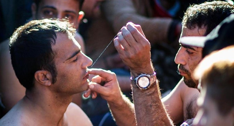 A man sews shut the mouth of a fellow migrant from Iran in protest at being held up at the Greece Macedonia border near Gevgelija