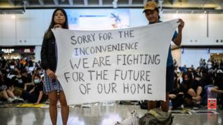 Hong Kong activists at an airport rally hold a banner reading: Sorry for the inconvenience we are fighting for the future of our home, 9 August 2019