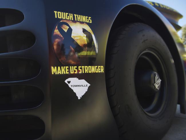 Tough things make us stronger is plastered on the side of a Batmobile driven to Jacob's funeral. Picture Rainier Ehrhardt/AP